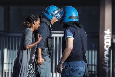 Un poliziotto in tenuta antisommossa e una donna eritrea di nome Genet si tengono la mano in piazza Indipendenza a Roma, durante lo sgombero di ieri (ANSA/ANGELO CARCONI)