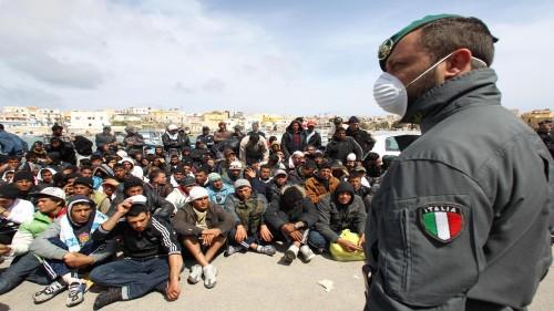 Gruppi di migrati riuniti per l'identificazione dalle forze dell'ordine a Lampedusa, oggi 29 marzo 2011. Nell'isola i migranti presenti sono 6.200, il dato e' fornito dall'ufficio della Regione siciliana. ANSA / FILIPPO VENEZIA